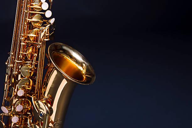 der schönen musik: golden saxophon gegen tiefblauen - altsaxophon stock-fotos und bilder