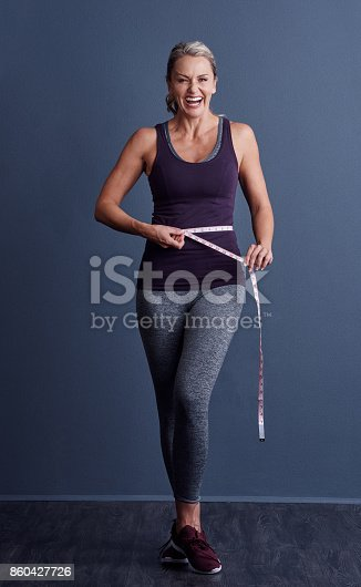 Studio portrait of an attractive mature woman standing with a tape measure around her waist against a blue background