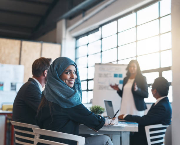 Making big moves in the boardroom Portrait of a smiling arab businesswoman attending a presentation with her colleagues in the office middle eastern culture stock pictures, royalty-free photos & images