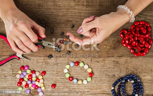 1074436306istockphoto Making bracelet of colorful beads. Female hands with a tool 1133605168