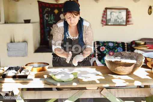 Making bread in traditional way in an outdoor kitchen older than a hundred years. seventh photo in series. Step five, putting the dough in trays, close-up.
