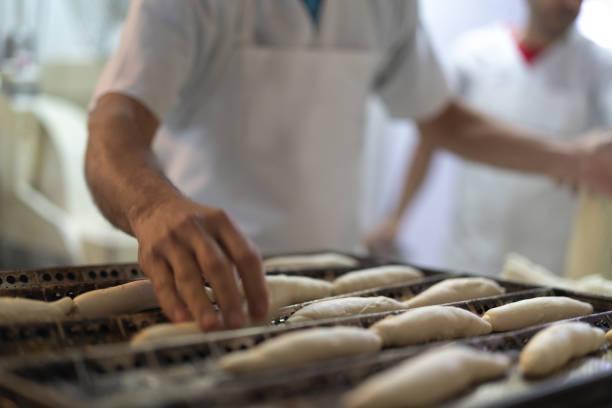 faire du pain à la boulangerie - boulanger photos et images de collection
