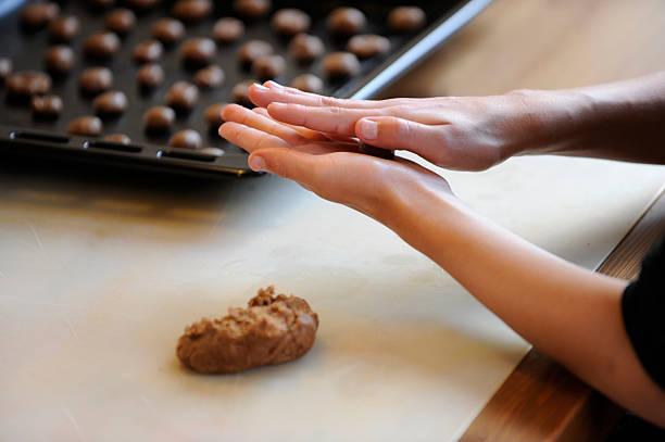 making brown spiced biscuit or pepernoten with dough - kruidnoten stockfoto's en -beelden