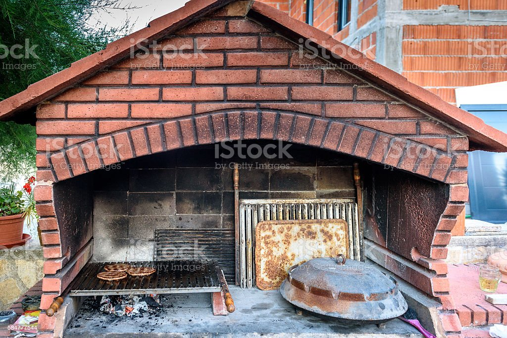 Making burgers in big barbecue grill fireplace with different ac stock photo