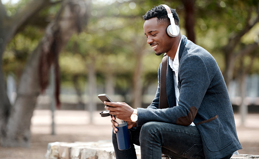 Shot of a young businessman using a smartphone and headphones in the city