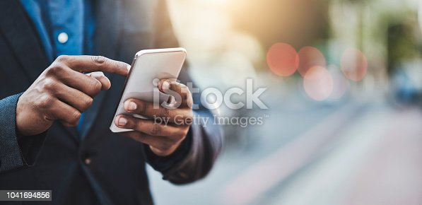Closeup shot of an unrecognizable businessman using a cellphone in the city