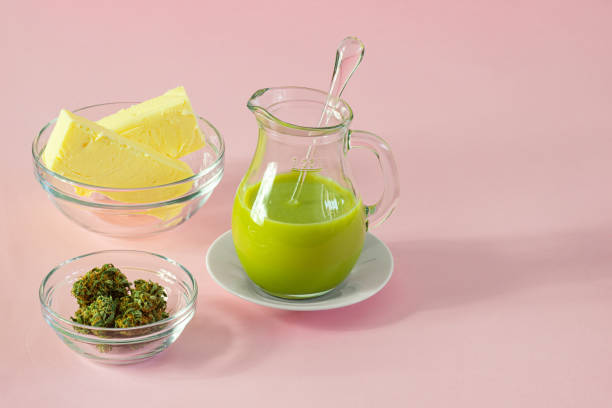 Making Cannabutter for Baking Edibles with Butter and Cannabis or Hemp on Pink Background stock photo