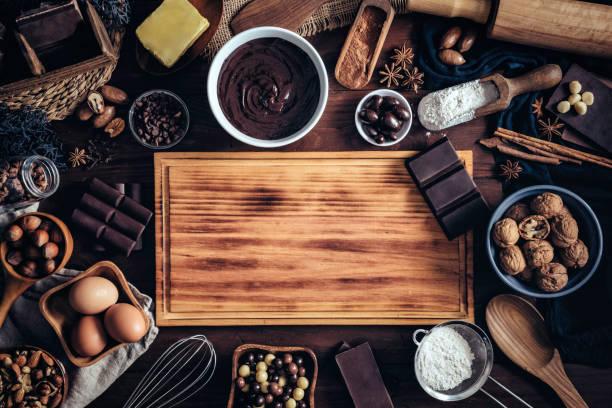 Fabrication de mousse au chocolat et ingrédients autour d'un cadre de planche à découper sur une table en bois cuisine rustique - Photo