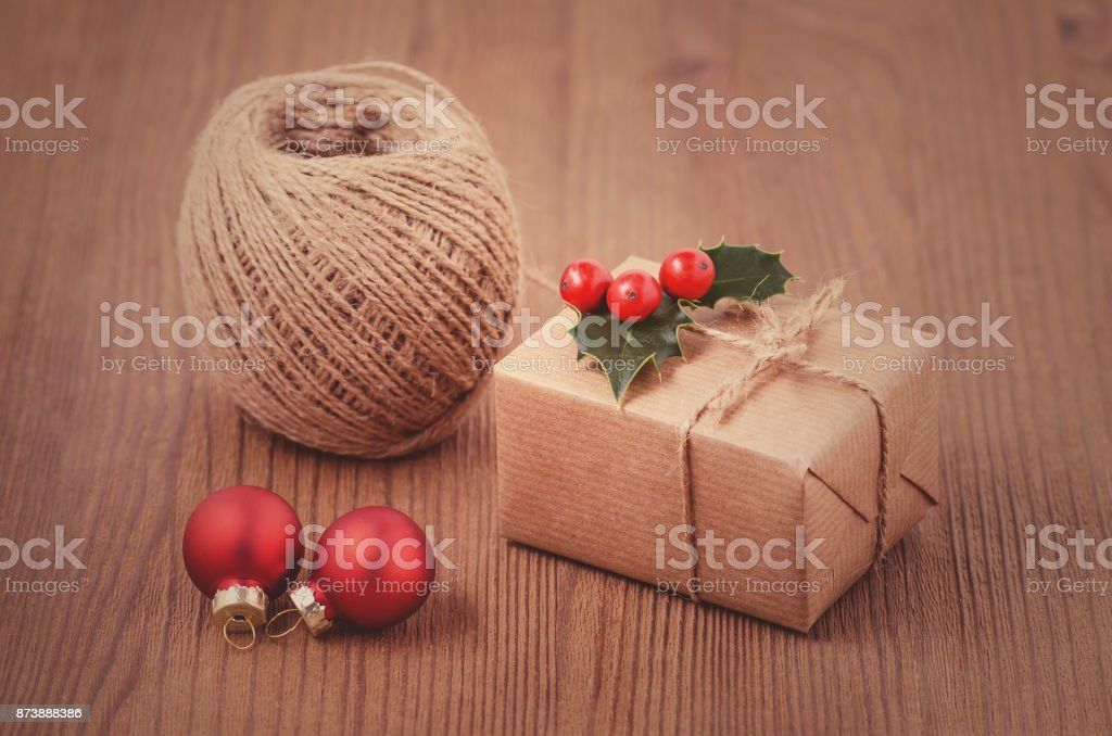 making christmas gits, a box with red holly berries, baubles and...