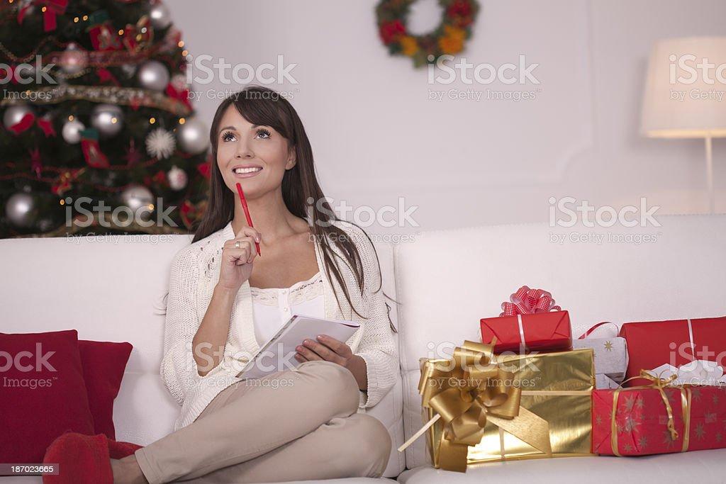 Woman sitting on sofa and making list for Christmas. Christmas tree...