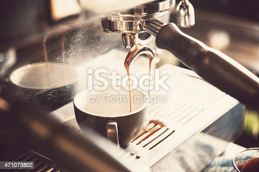 Coffee being poured into a mug by a coffee machine in a busy inner city cafe.