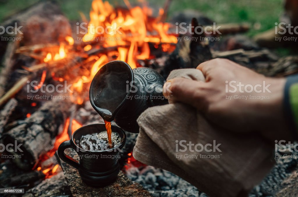 Making coffee process on the campfire. Man pour coffe in potter cup stock photo