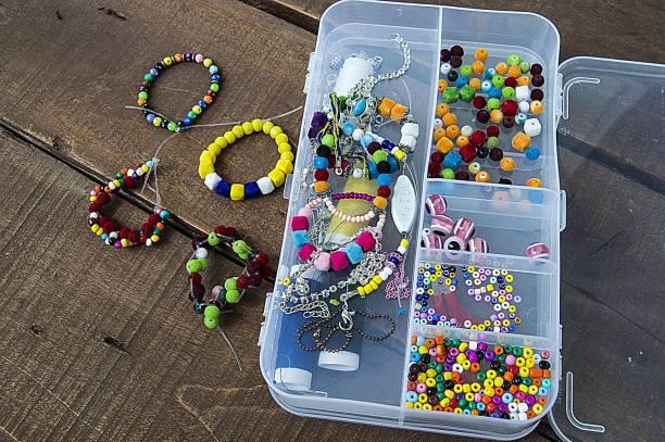 machen bunte armbänder für kinder, die armbänder und ornamenten aus bunten perlen, ketten und armbänder aus bunten perlen zu machen, - armband i gummi stock-fotos und bilder