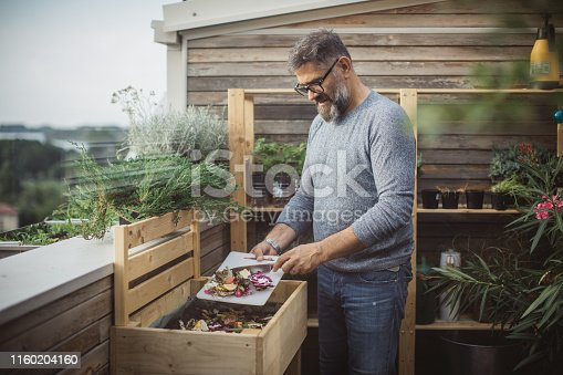 After preparing vegetable meal for cooking, mature men making compost from leftovers.