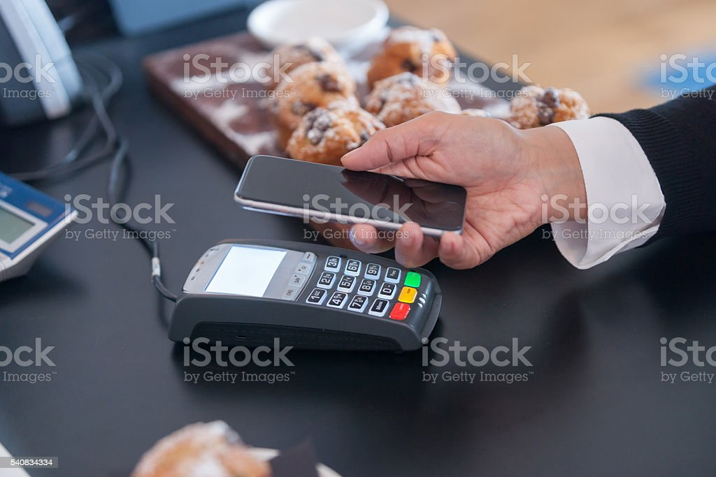 Making contactless payment in cafe with mobile phone. stock photo