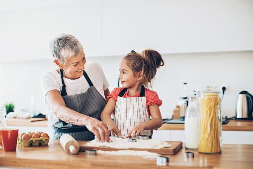 Senior woman and a small girl preparing cookies