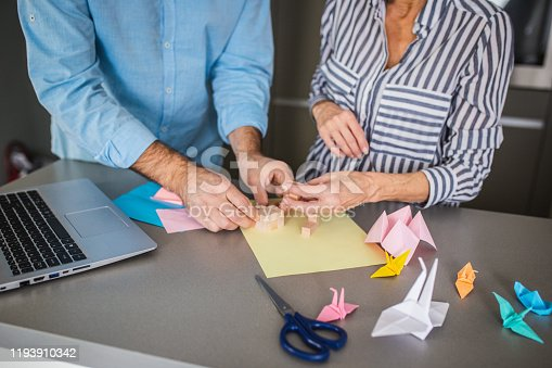 Couple is at home learning from youtube how to make origami