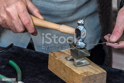 1130936245istockphoto Making crafts with a small anvil and a hammer 923401752