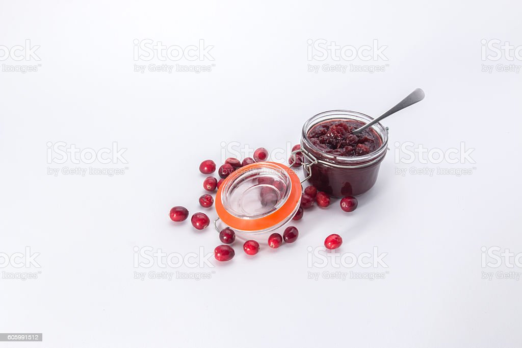 Making cranberry relish/sauce,   filled small kilner style jar scattered cranberries stock photo