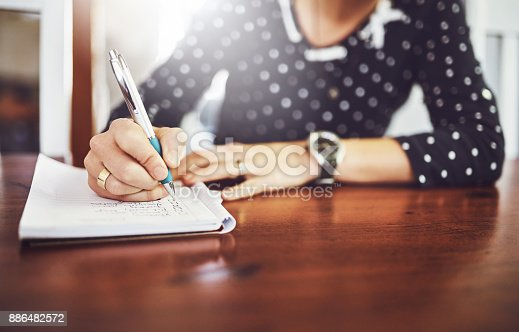 Shot of a unrecognizable woman writing in a book with a pen on a dinner table at home