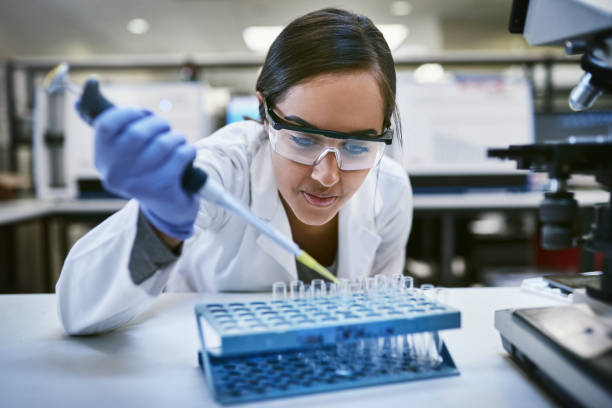 Making daily strides in the field of science Shot of a young woman transferring liquid from a pipette to a test tube in a laboratory biochemist stock pictures, royalty-free photos & images