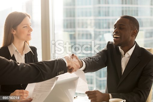 istock Making deal and shaking hands with smiling satisfied african-american client 695760214