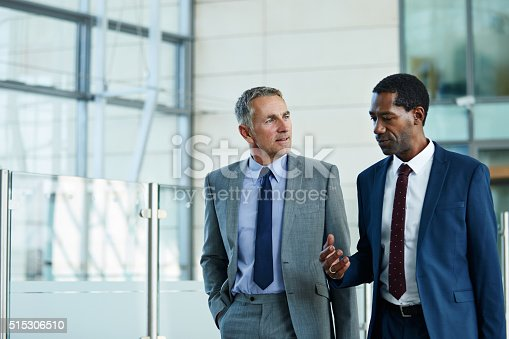 Shot of two businessmen walking and talking together in the lobby of an office building