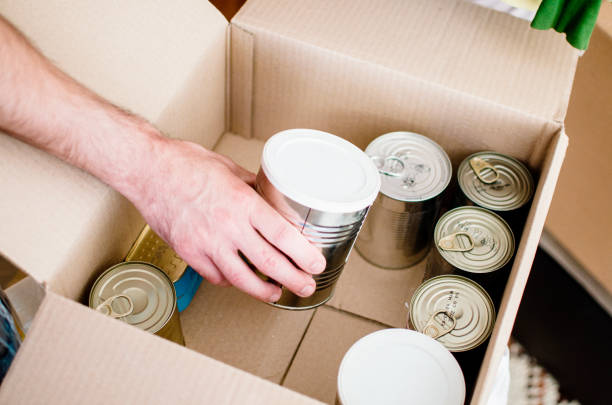 Making Donations To Community Food Bank Volunteer work at food bank,loading cardboard box with canned food.Help for Poor people. charitable foundation concept.Close up on male hand packing food food drive stock pictures, royalty-free photos & images