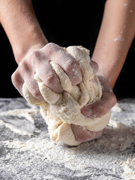 Making dough by female hands at bakery Making dough by female hands at bakery, Production of flour products baking bread stock pictures, royalty-free photos & images