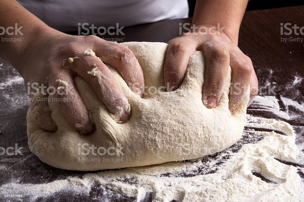 Making dough by female hands at bakery stock photo