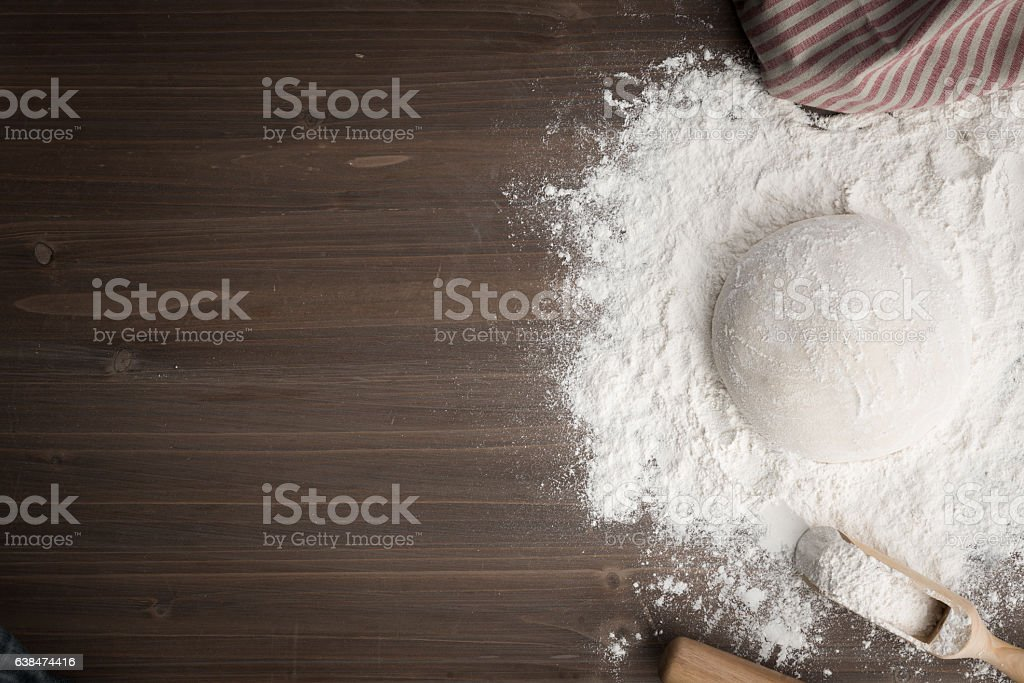 Making dough over wooden table stock photo
