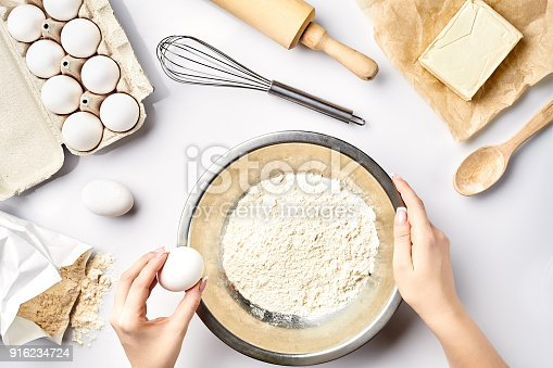 istock Making dough top view. Overhead of baker hands break egg on flour. Cooking ingredients for pastry on white table 916234724