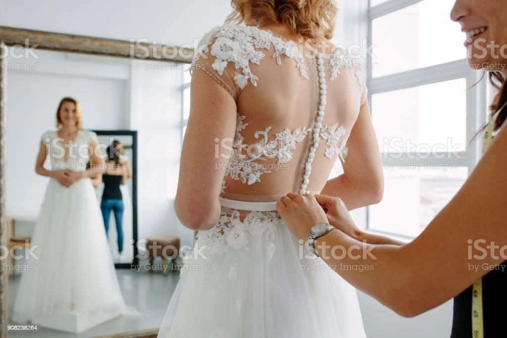 Making final touch on tailor made gown in bridal shop stock photo