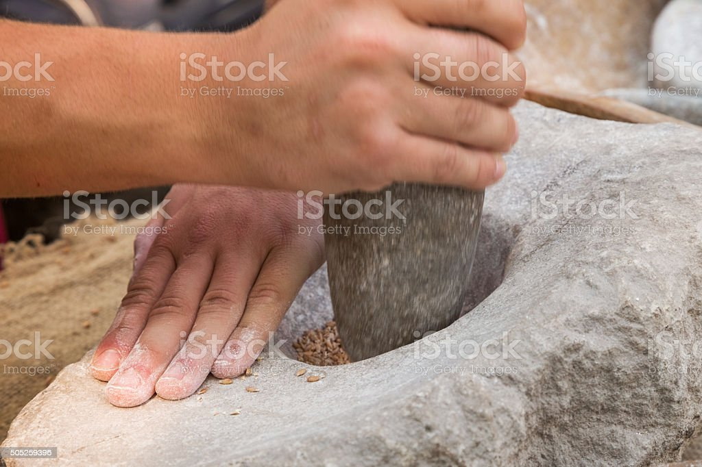 Making flour in a traditional way for the Neolithic era stock photo