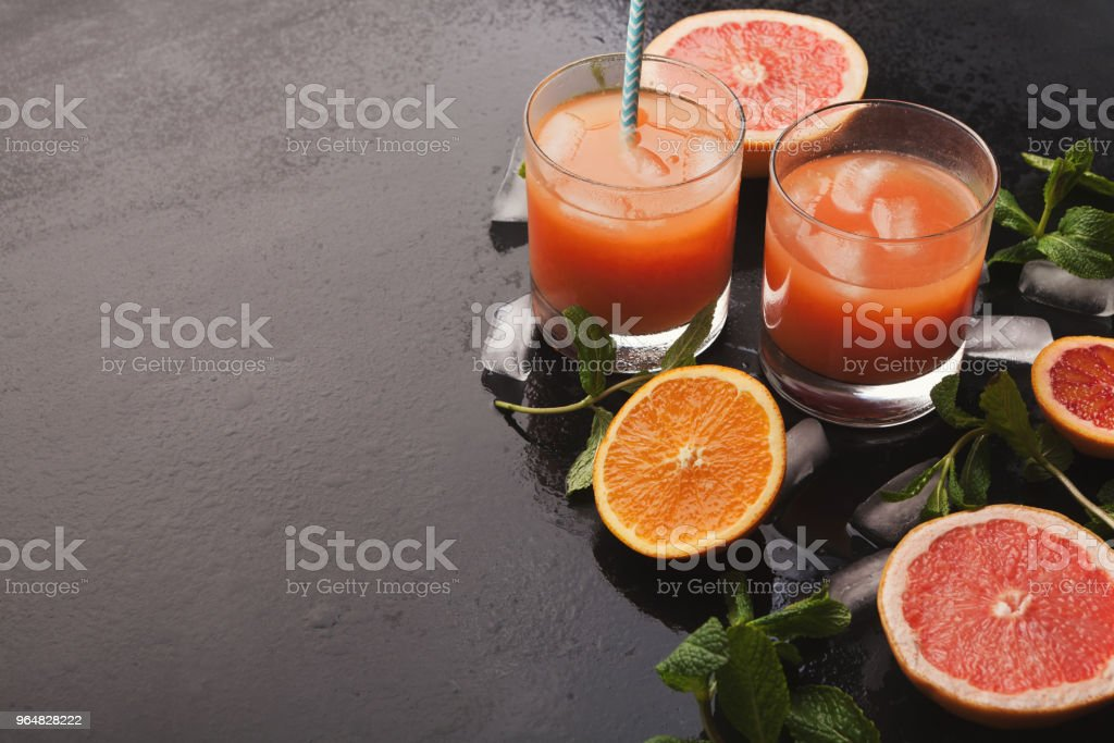 Making fresh citrus juice at home, ingredients on black table royalty-free stock photo