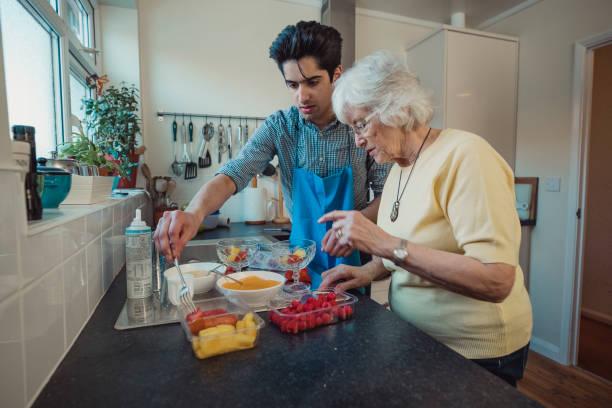 making fruit compote with grandmother - voluntário imagens e fotografias de stock