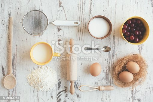 Cherries and kitchen utensils on wooden table, wooden spoon, rolling pin, colander, wire whisk, bowl and cup. Ingredients also: eggs, cherries, cinnamon, milk, flour and sugar.