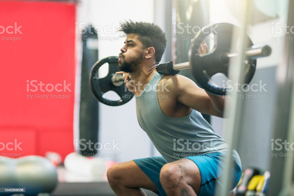 Young athlete doing cross training with a barbell at the gym.