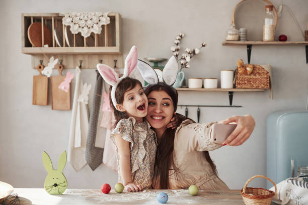 Lustige Gesichter machen. Mutter und Tochter in hästigen Ohren zur Osterzeit haben etwas Spaß in der Küche am Tag – Foto