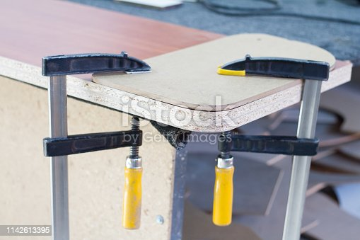 istock Making furniture in the process, gluing furniture shields for making furniture. 1142613395