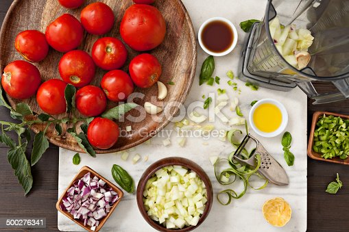 An overhead close up shot of the ingredients for gazpacho and a blender.