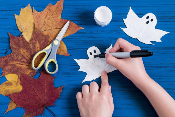Making ghosts from maple leaves to Halloween. Step 4 stock photo