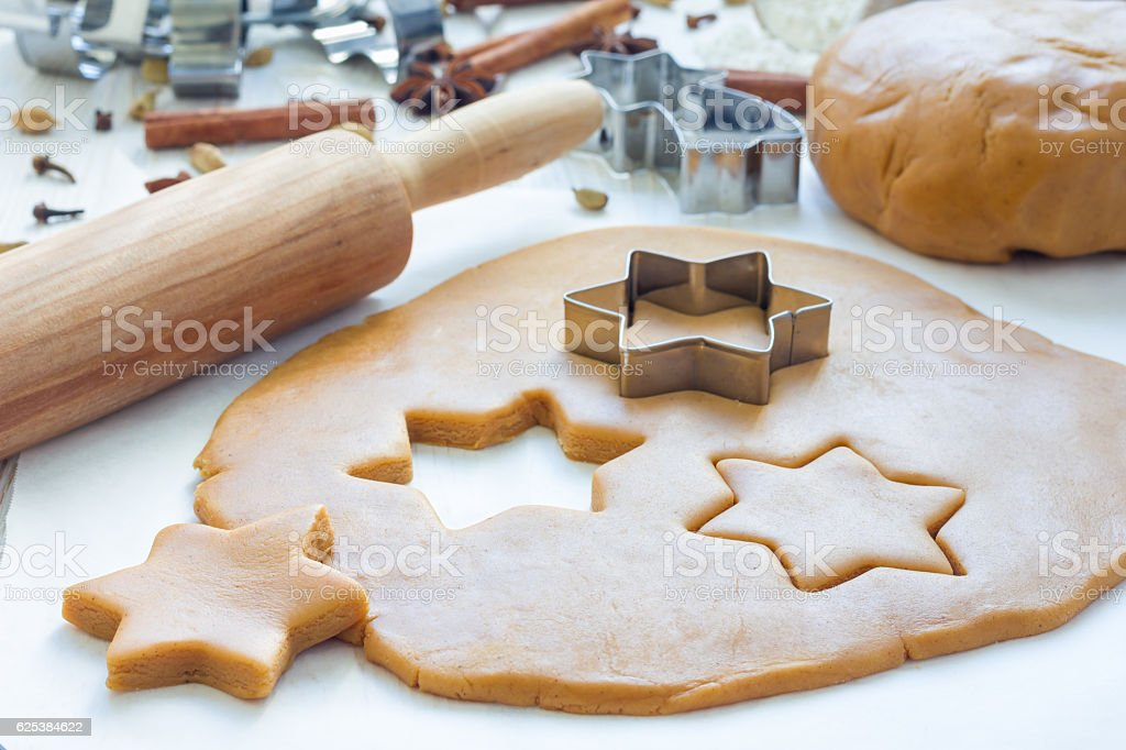 Making gingerbread cookies. Dough, cutter and rolling pen on table stock photo