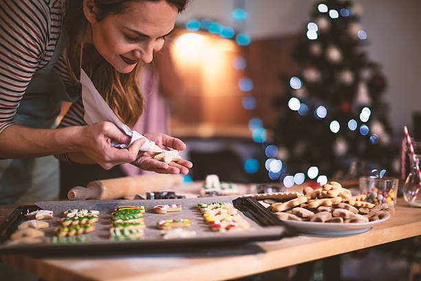 making gingerbread cookies for christmas - christmas cookies stock pictures, royalty-free photos & images
