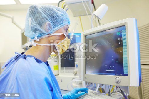 Surgical nurse monitoring a patient's vitals in an operating room