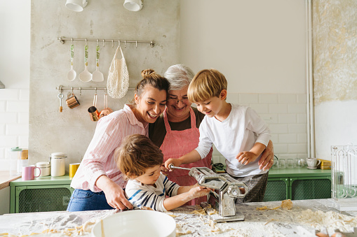 Photo of cute little boys learning how to make homemade pasta, assisted by their grandmother and mother in the kitchen; rolling out the pasta dough using the manual pasta maker; having a great time while making food and enjoying each other's company.