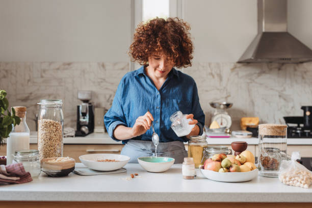 Making Granola at Home: Woman Adding Coconut Oil into a Bowl With Rolled Oats and Spices Homemade baked granola: woman adding ingredients into a bowl of rolled oats in the kitchen. coconut oil stock pictures, royalty-free photos & images