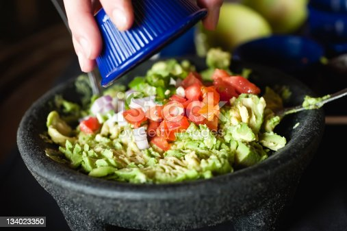 woman pouring diced tomatoes and onions over a guacamole