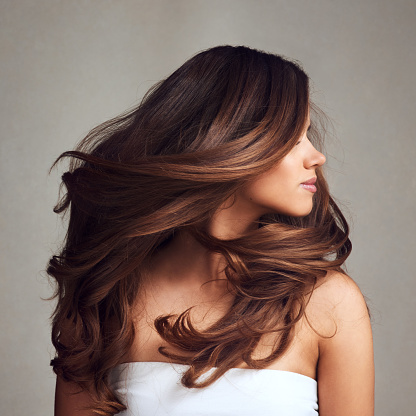 Studio shot of a young beautiful woman with long gorgeous hair posing against a grey background