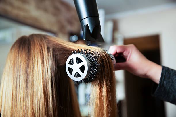 Making hairstyle using hair dryer. stock photo